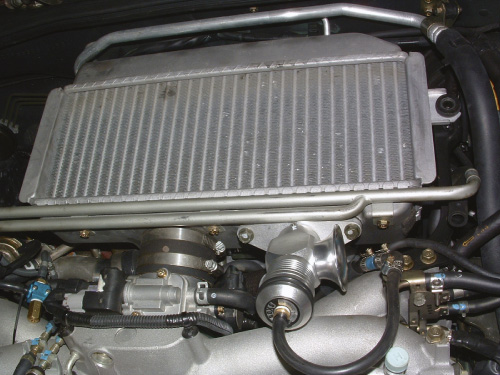 The intercooler cools the pressurized air to create a denser intake charge.